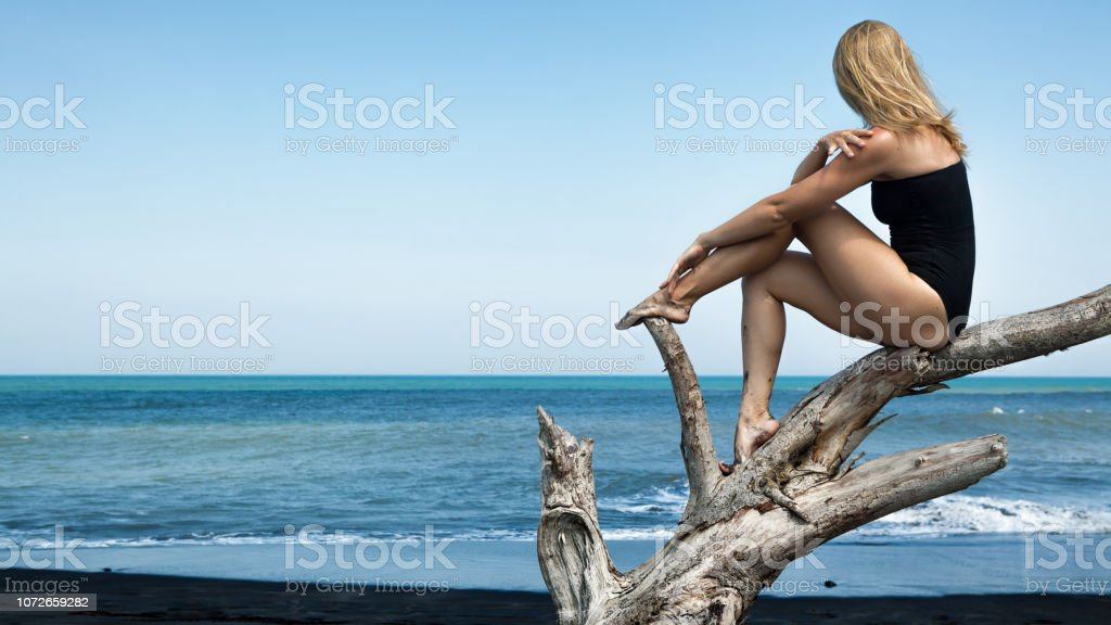 Girl sit and relax on tree branch, look at sea stock photo