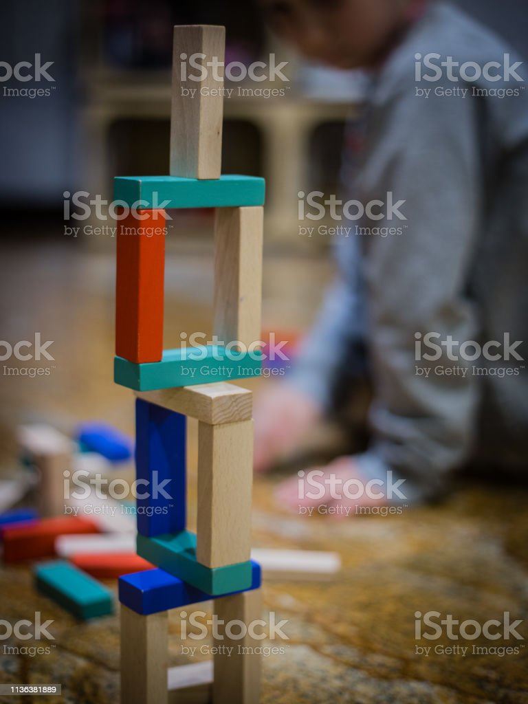 A girl siting at background and a wood game on the floor. Some bricks...
