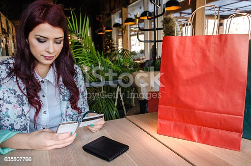 istock Girl sits at the table and buys over the Internet 635807766