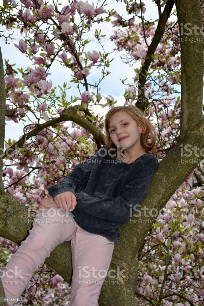 A girl sits in a magnolia tree and smiles forwards zbiór zdjęć royalty-free