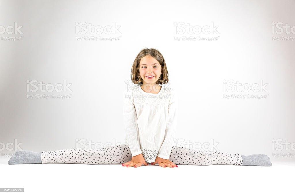 Girl sits in splits on floor. royalty-free stock photo