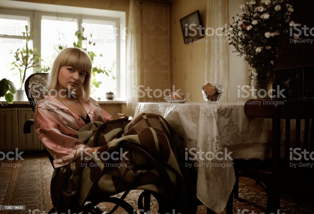 Girl sits in the rocking-chair about a table royalty-free stock photo