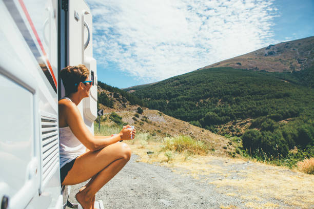 Girl sits on a motor home step Side view of a young woman is sitting on a caravan step and holding a cup on a holiday adventure trip stop. Copy space area available caravan photos stock pictures, royalty-free photos & images