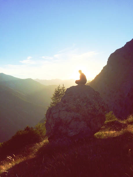 Girl sits on a rock in the sunset in alps stock photo