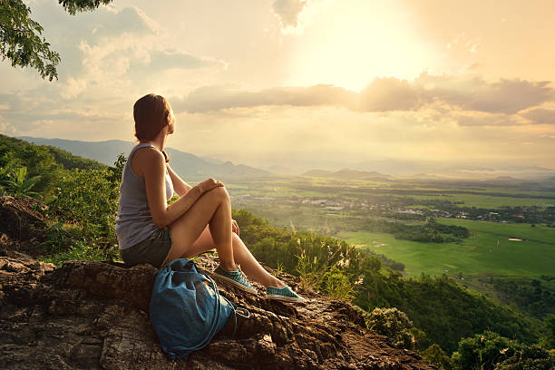 Girl sits on edge cliff and looking at sun valley stock photo