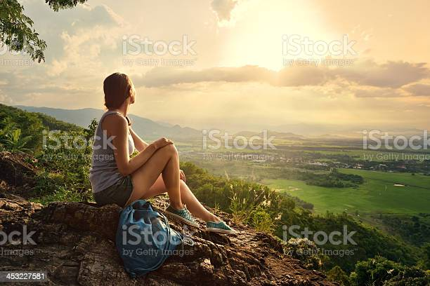 Photo of Girl sits on edge cliff and looking at sun valley