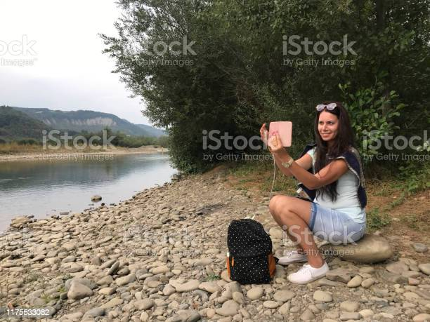 Girl sits on the shore of a mountain river and looks into a nearby picture id1175533082?b=1&k=6&m=1175533082&s=612x612&h=wfd2wk0bf8ejt4vk1lfm5pnwlllbjo5jnkn2donfjss=