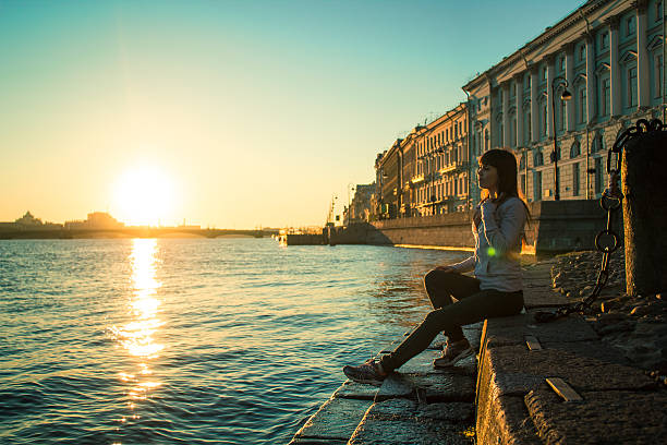 Girl sits on the steps of the river. stock photo
