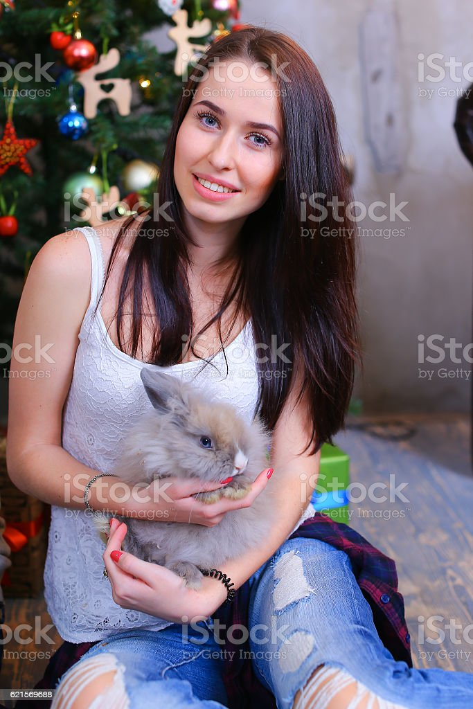 Girl sits smiling and posing with rabbit in decorated studio foto stock royalty-free