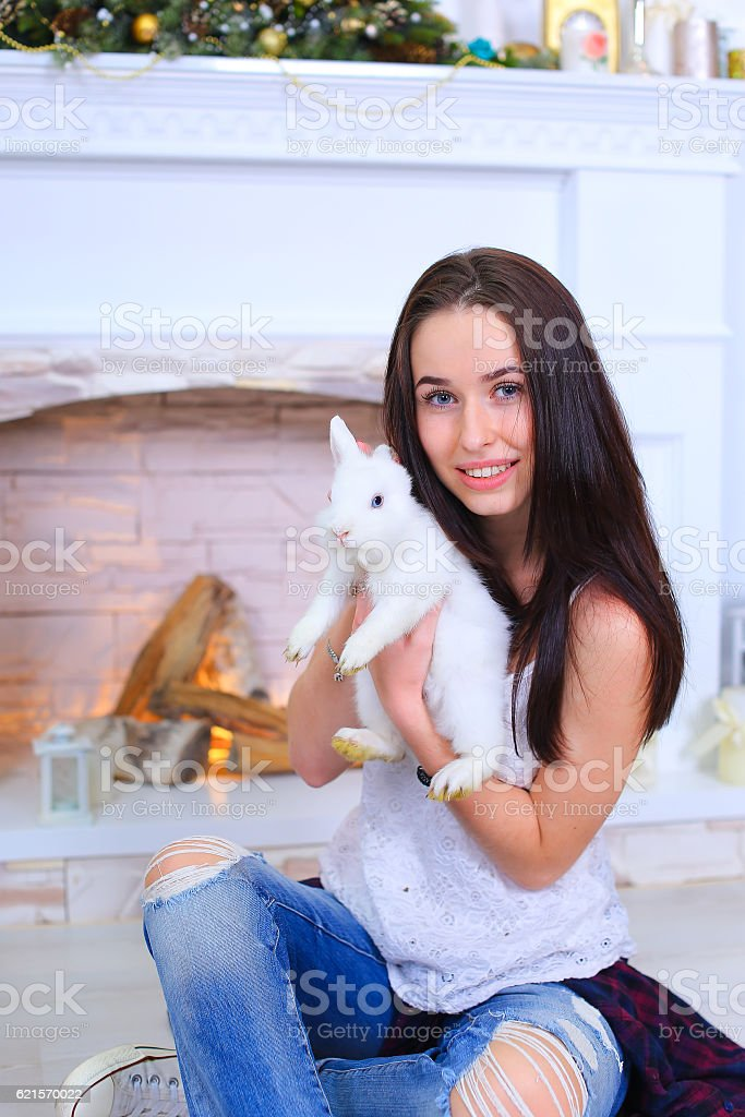 Girl sits smiling and posing with rabbit in decorated studio photo libre de droits