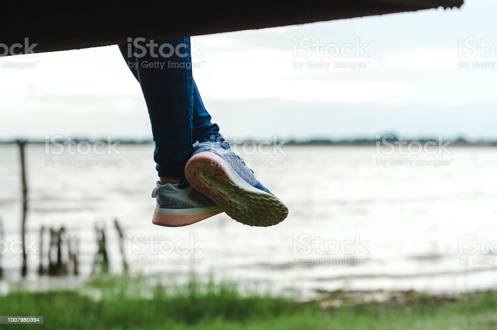 Girl sitting alone legged. On the bridge to the air Cool, comfortable, cool in the evening at the sunset happily. Self-help concept stock photo