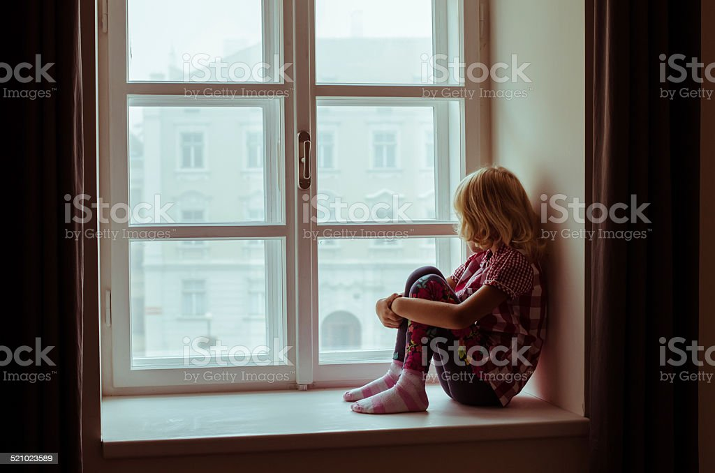 girl sitting alone stock photo