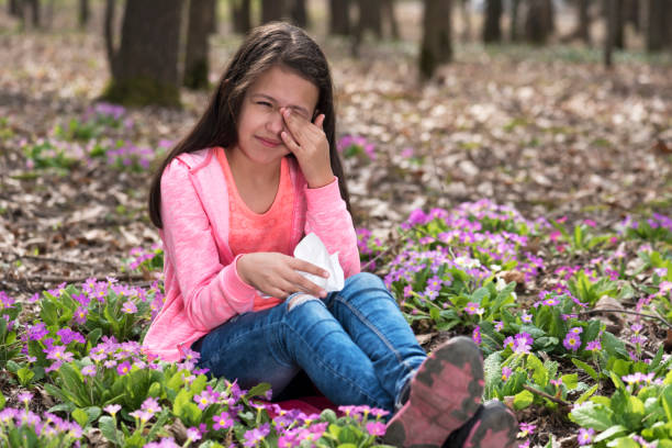 Girl sitting among primroses and rubbing her eyes Girl sitting among primroses and rubbing her eyes. Selective focus antihistamine stock pictures, royalty-free photos & images