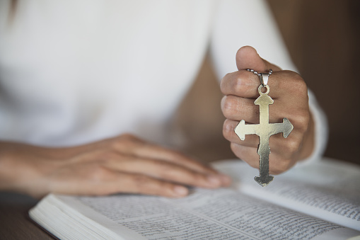 A girl sitting and studying the scriptures. The other hand is holding a cross. Christian education concepts The Holy Scriptures open and pray to God.