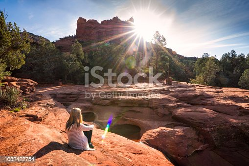 A blond teenage girl sits facing the sun on the rocks overlooking the Seven Sacred Pools, Sedona, Arizona, USA