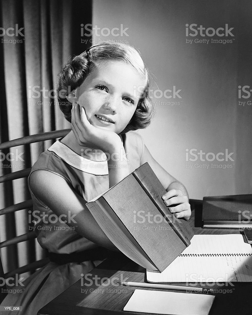 Girl sitting at table, holding book, daydreaming royalty free stockfoto