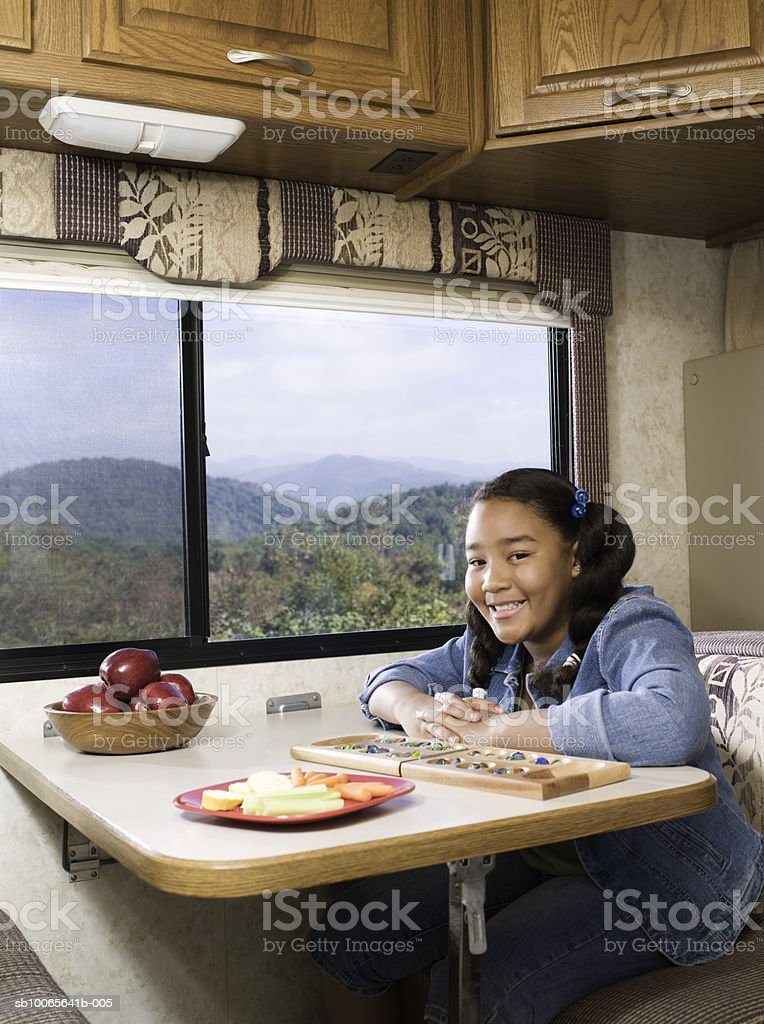 Girl (10-11) sitting at table in motorhome, smiling, portrait foto de stock royalty-free
