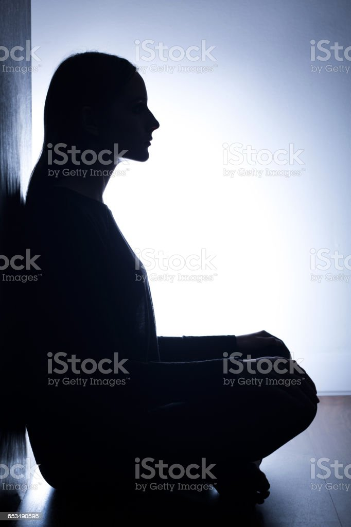 Girl sitting back to wall stock photo