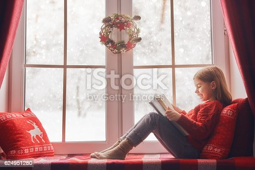 istock girl sitting by the window 624951280