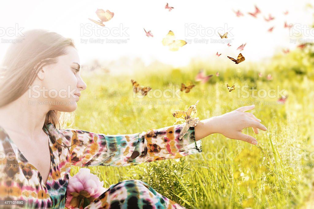 Girl sitting in a meadow in swarm of flitting butterflies. stock photo