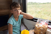 A girl sitting in a reserved seat carriage in a train thoughtfully looks into the frame