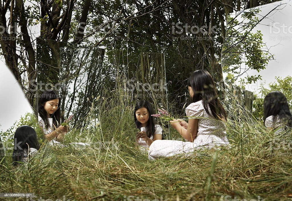 Girl (8-9) sentado en la hierba, refleja en cuatro de los espejos foto de stock libre de derechos