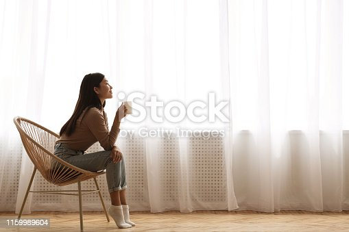 Calm Morning. Girl Sitting In Modern Chair, Enjoying Coffee In Front Of Window, Side View