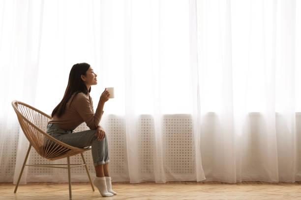 chica sentada en la silla moderna, disfrutando del café de la mañana - café bebida fotografías e imágenes de stock
