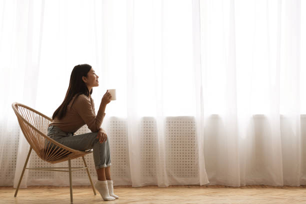 Girl Sitting In Modern Chair, Enjoying Morning Coffee Calm Morning. Girl Sitting In Modern Chair, Enjoying Coffee In Front Of Window, Side View relaxation stock pictures, royalty-free photos & images