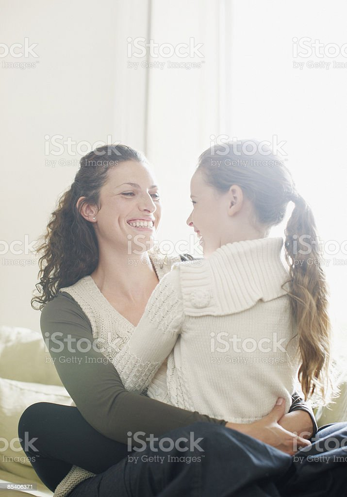 Girl sitting in mothers lap royalty-free stock photo