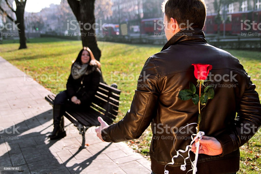 Girl sitting in park and boyfriend approach with red rose - foto de acervo