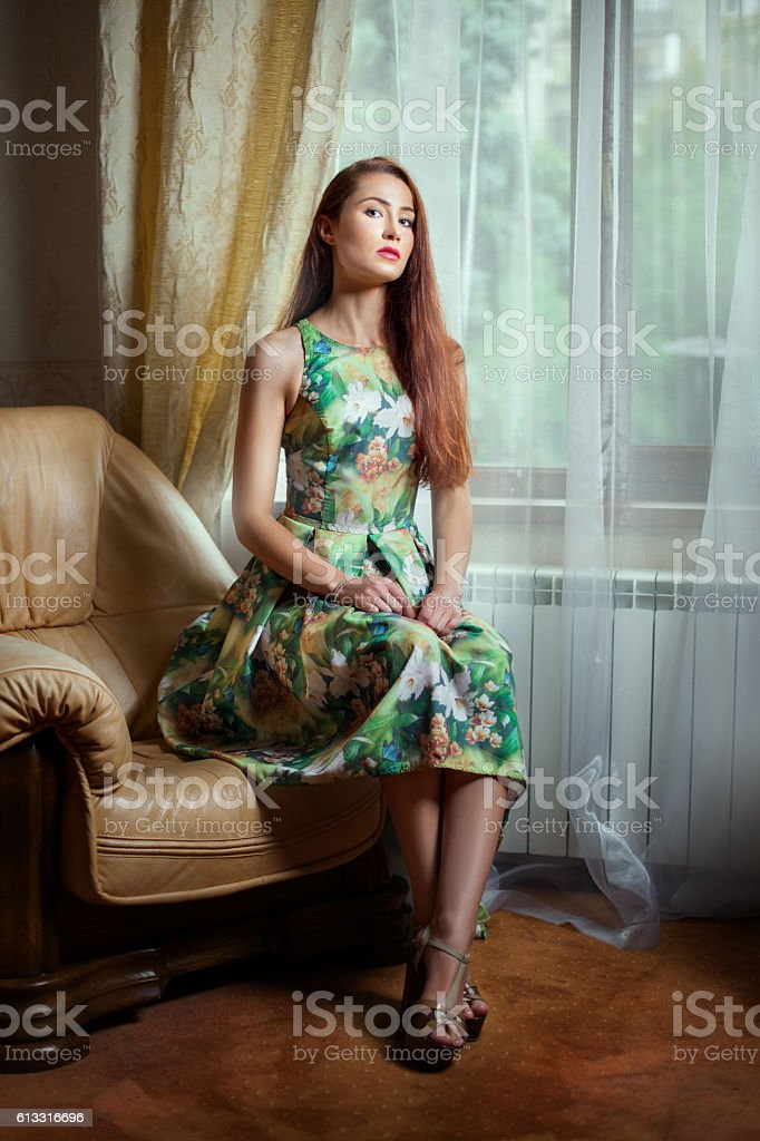 Girl sitting on a an armchair. stock photo