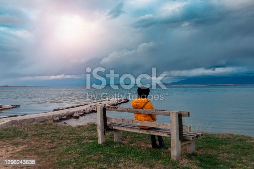 Girl sitting on a bench by the sea at sunset.