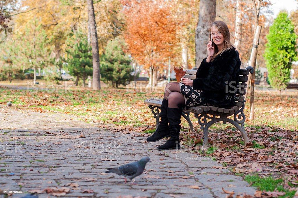 Fille assis sur un banc dans le parc sur une journée d'automne photo libre de droits