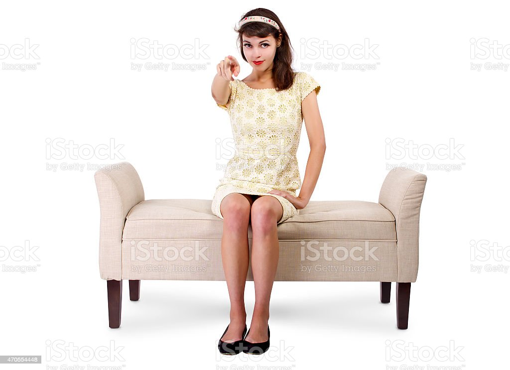 Girl Sitting on a Chaise Lounge Sofa Pointing Forward stock photo