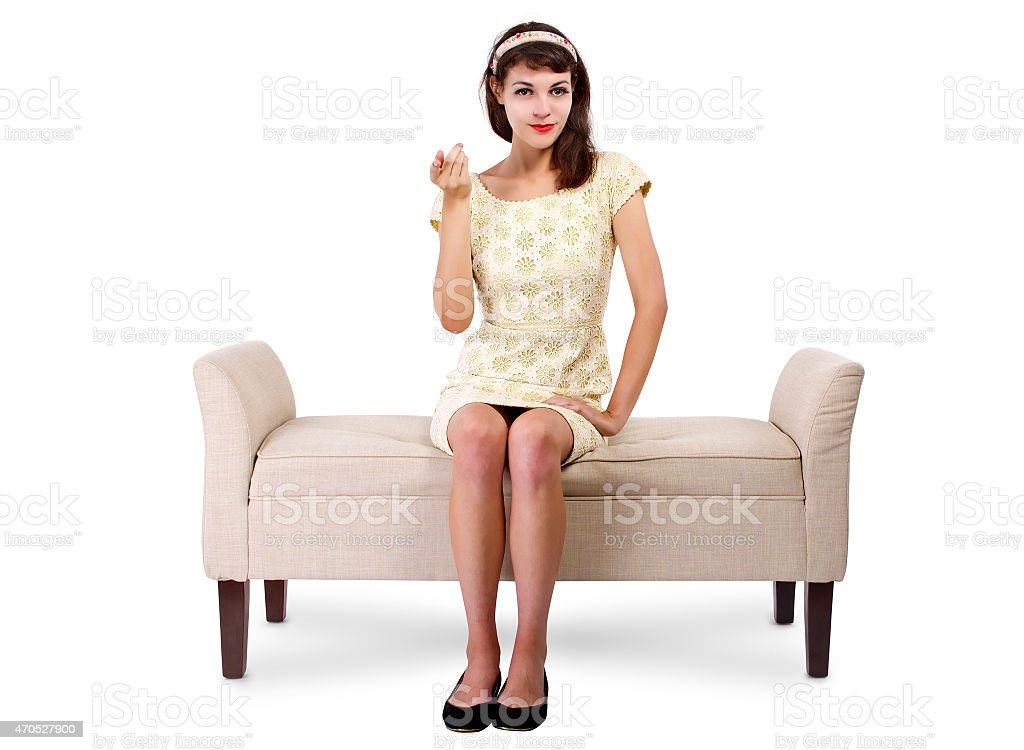 Girl Sitting on a Chaise With a Come Here Gesture stock photo