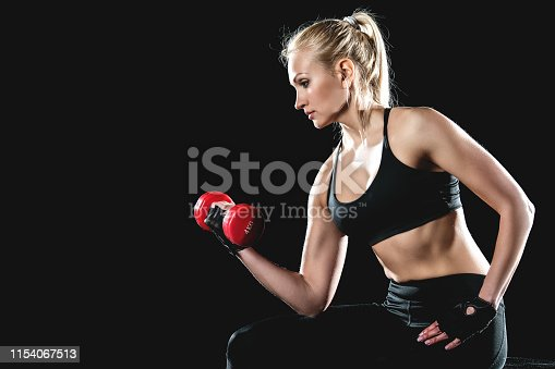 istock Girl sitting on a cube to gym and pump up her biceps using dumbbells. 1154067513