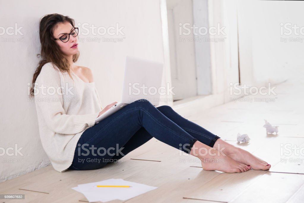 Girl sitting on a floor and writting a paper stock photo