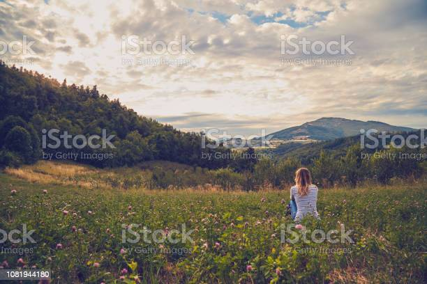 Photo of Girl sitting on a green meadow and watching the countryside landscape.