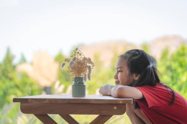 Chica sentada en una mesa con un frasco de flores para los niños aman el concepto de la naturaleza. - foto de stock