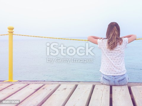 Girl sitting on a wooden mole / pier and looking at the ocean.