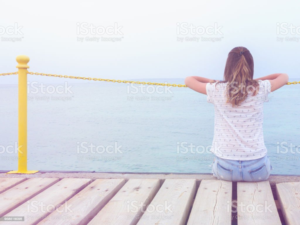 Girl sitting on a wooden mole / pier and looking at the ocean. stock photo