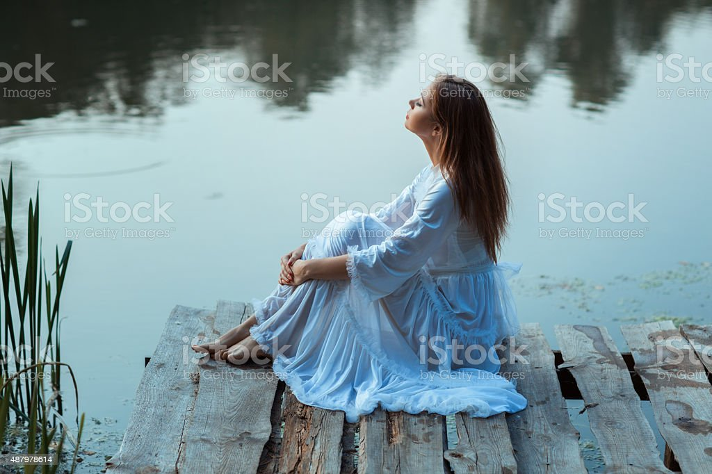 Girl sitting on a wooden pier and dreams. stock photo