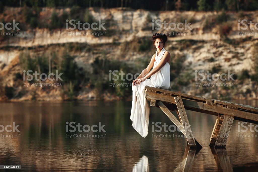 girl sitting on a wooden pier on a river or a lake royalty-free stock photo