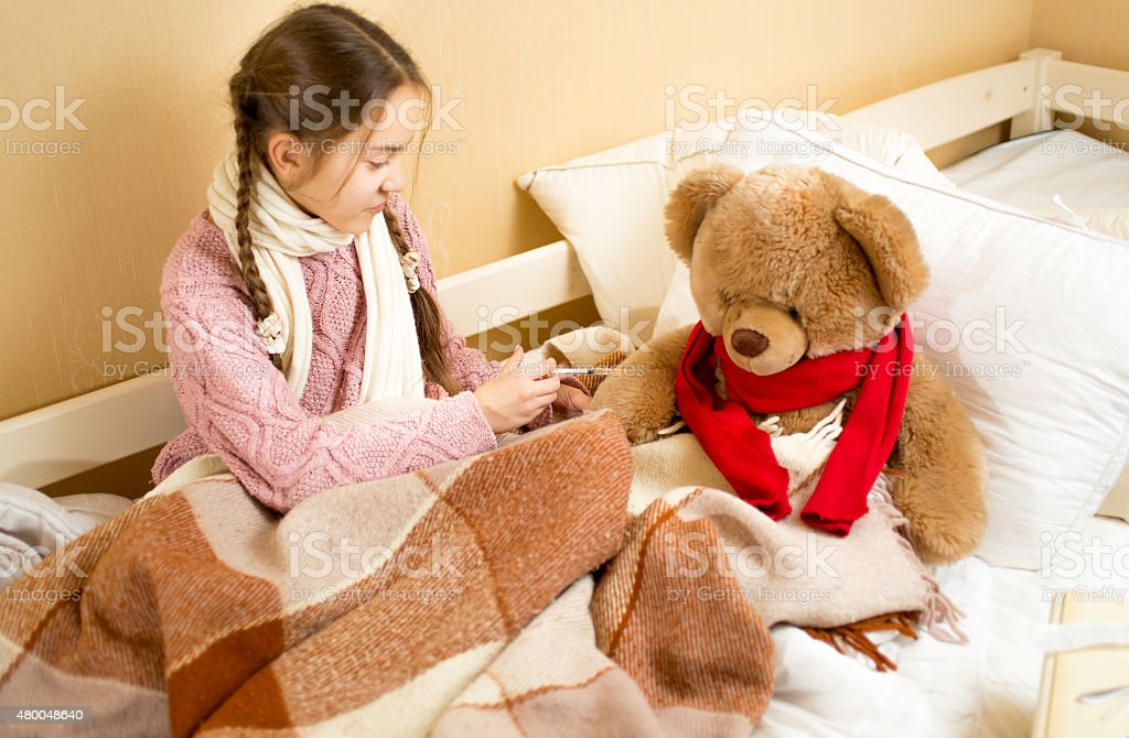 girl sitting on bed and doing injection to teddy bear stock photo