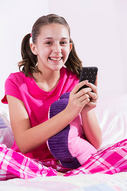 girl sitting on bed in pajamas texting - pigtails stock photos and pictures