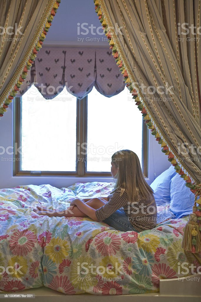 Girl (8-9) sitting on bed photo libre de droits
