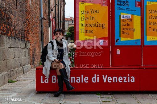 VENICE, ITALY - MAY, 09: Girl sitting on bench during the 58th International Art exhibition of Venice biennale titled May You Live In Interesting Times  on May 09, 2019\