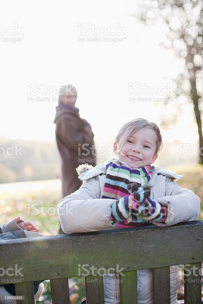 Girl sitting on bench outdoors in autumn royalty-free stock photo