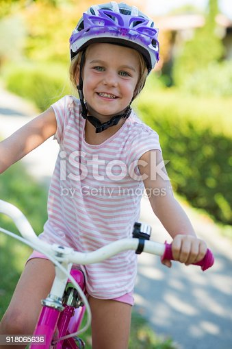 Portrait of girl sitting on bicycle.